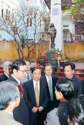 米軍爆撃犠牲者記念碑を訪問し献花し説明を受ける志位委員長ら
