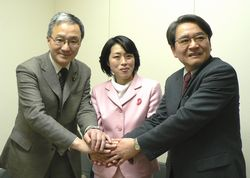 堅く握手する田村さん、緒方さん、笠井さん