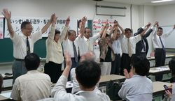 区議候補らとともに手を上げてこたえる笠井議員